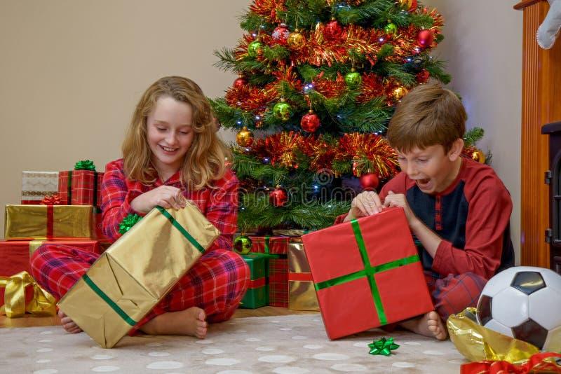 Crianças que abrem presentes de Natal fotos de stock