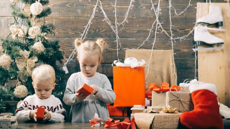 Crianças que abrem presentes do Xmas inverno que nivela em casa Criança de sorriso feliz com caixa de presente do Natal imagem de stock