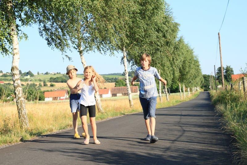 Crianças que andam na estrada com árvores imagens de stock royalty free