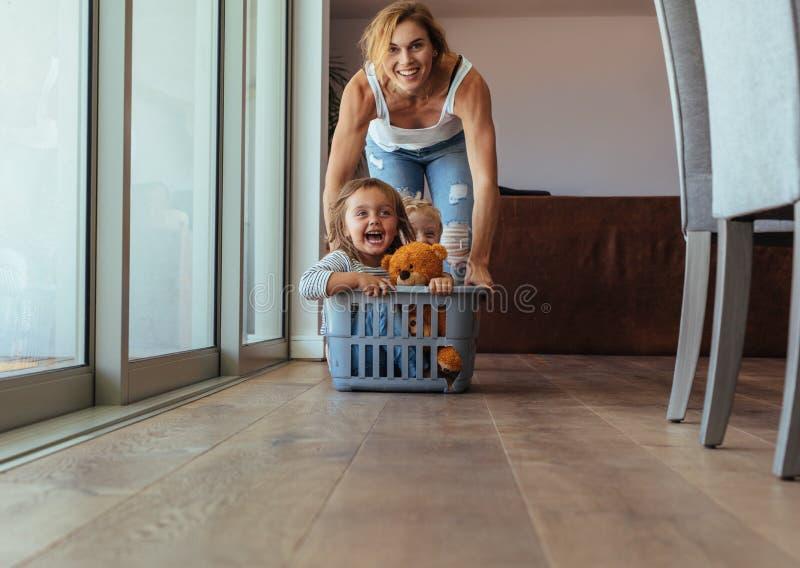Crianças que apreciam em casa com mãe fotografia de stock royalty free