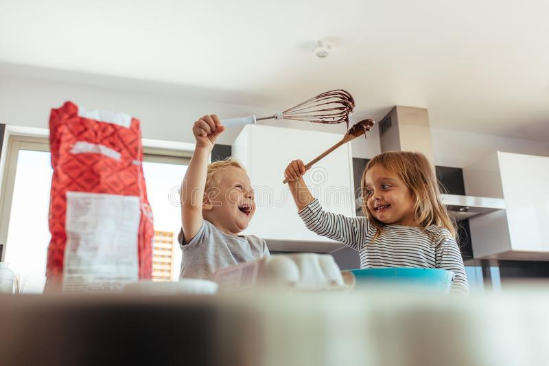 Crianças que apreciam fazendo o bolo na cozinha fotos de stock