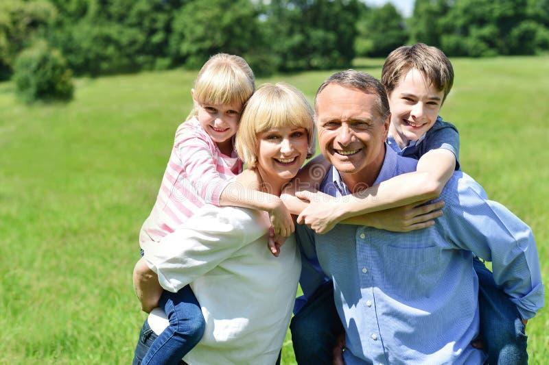 Crianças que apreciam o passeio leitão em pais para trás fotografia de stock royalty free