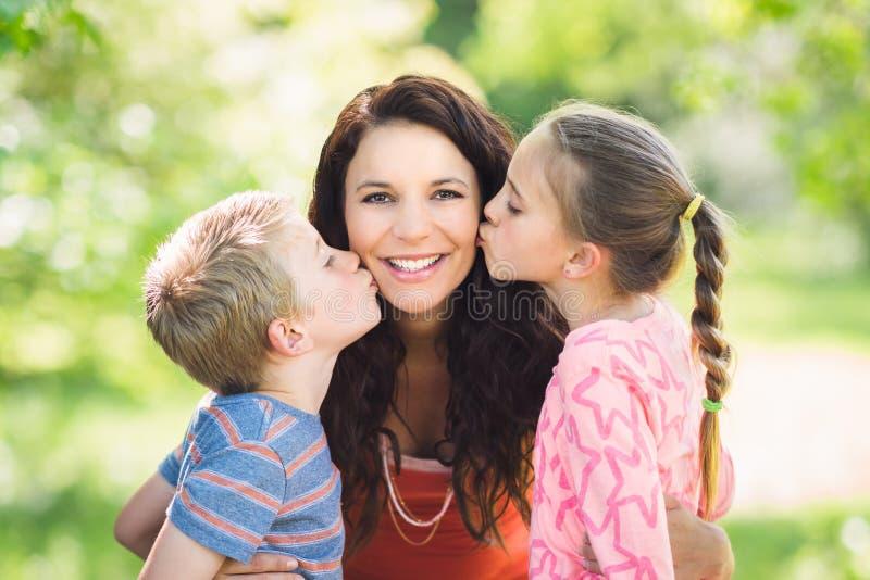 Crianças que beijam a mãe foto de stock