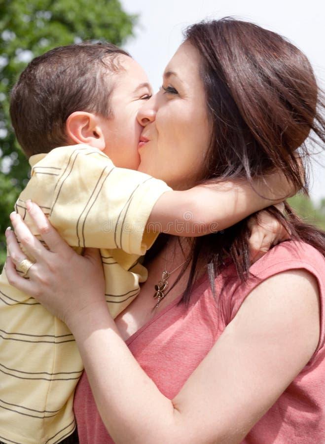Crianças que beijam sua mamã no parque fotos de stock royalty free