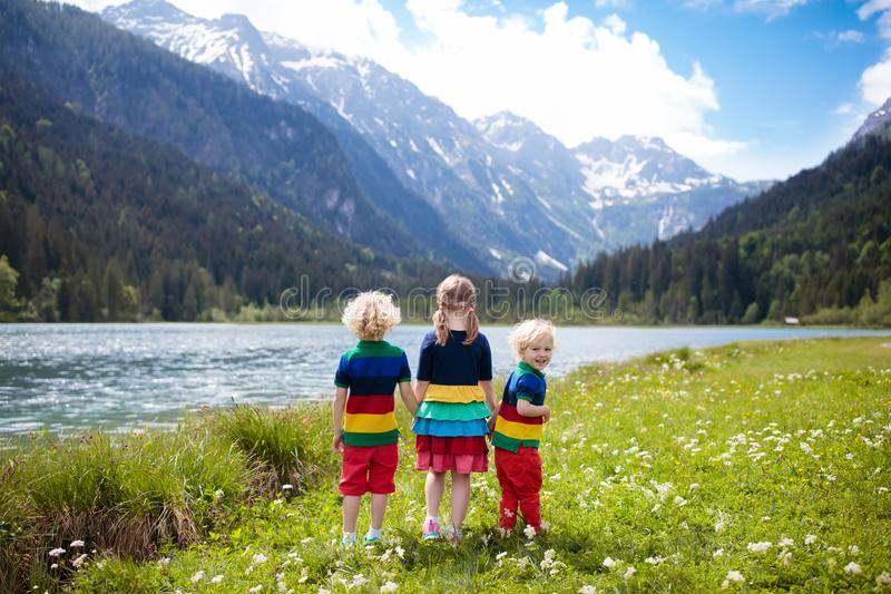 Crianças que caminham no campo de flor no lago da montanha imagens de stock