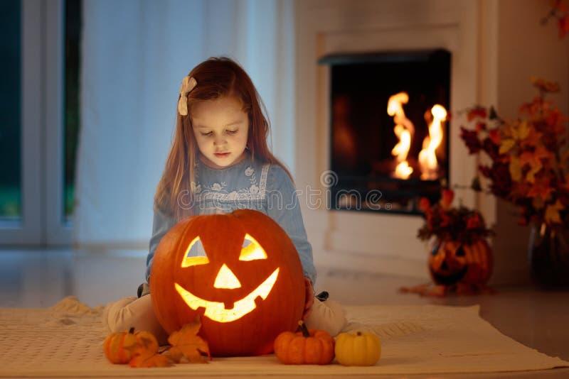 Crianças que cinzelam a abóbora em Dia das Bruxas Truque ou deleite fotografia de stock