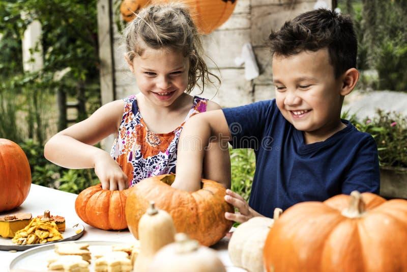 Crianças que cinzelam o ` do jaque-o de Dia das Bruxas - lanternas fotografia de stock