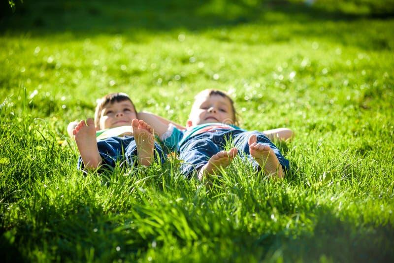 Crianças que colocam na grama Piquenique da família no parque da mola imagens de stock royalty free