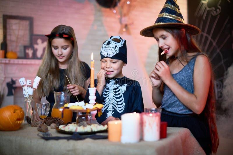 Crianças que comem doces no partido de Dia das Bruxas foto de stock