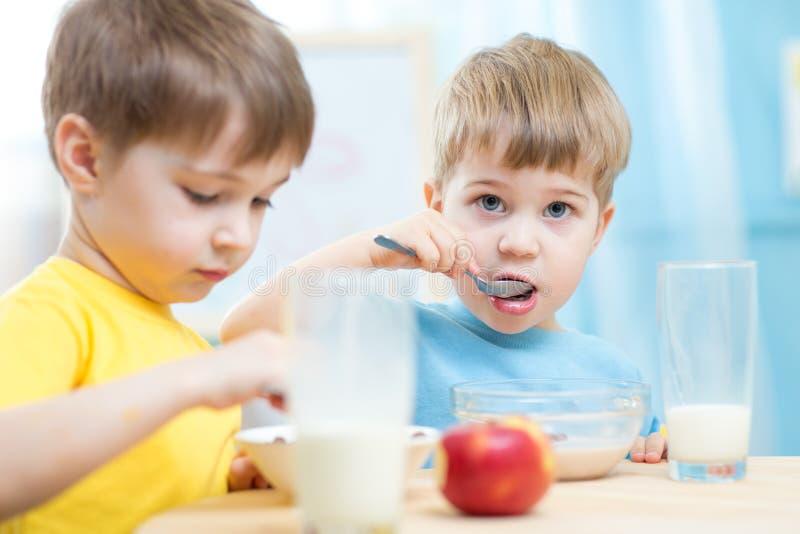 Crianças que comem o alimento saudável em casa ou o jardim de infância foto de stock royalty free