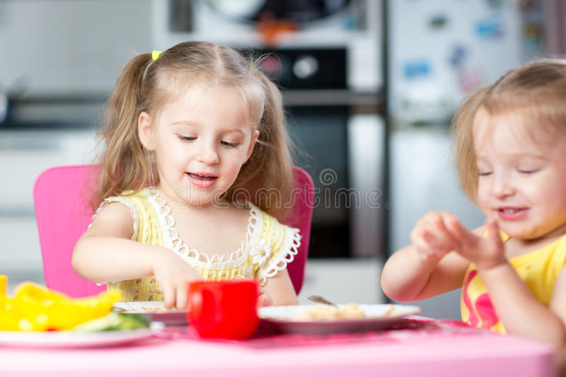 Crianças que comem o alimento saudável no berçário ou em casa fotos de stock