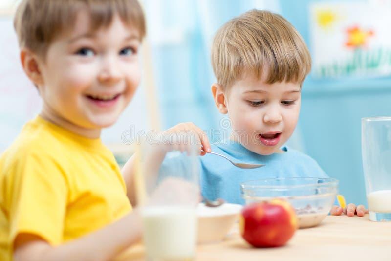 Crianças que comem o alimento saudável no jardim de infância foto de stock