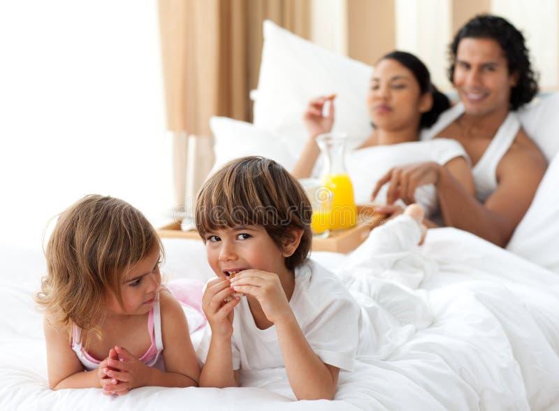 Crianças que comem o pequeno almoço com seus pais fotos de stock royalty free