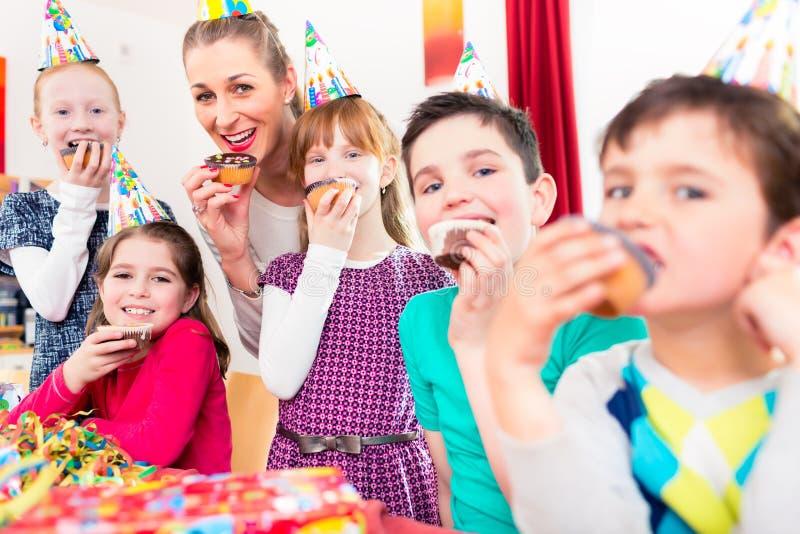 Crianças que comem os queques que comemoram o aniversário fotos de stock
