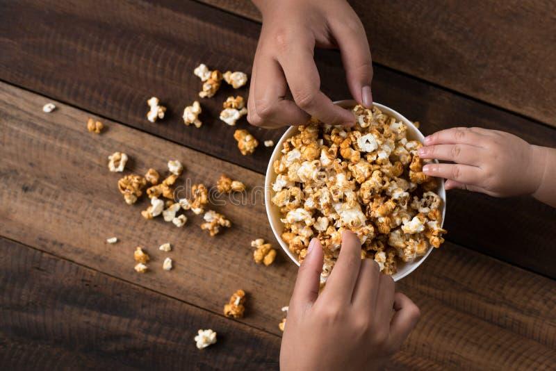 3 crianças que compartilham comendo a pipoca em uma bacia imagens de stock