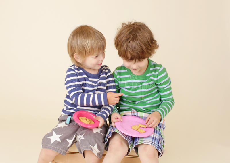 Crianças que compartilham de um petisco, alimento, a forma das crianças fotografia de stock royalty free