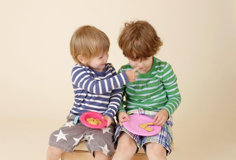 Crianças que compartilham de um petisco, alimento, a forma das crianças fotografia de stock