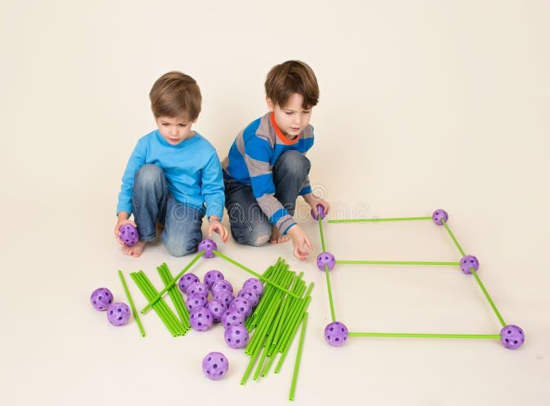 Crianças que compartilham do grupo da construção, partes de construção imagem de stock royalty free