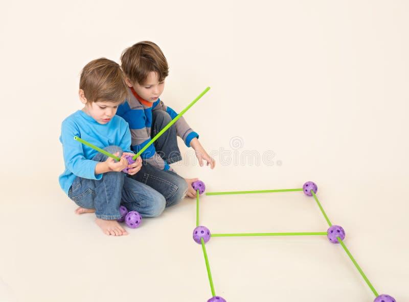 Crianças que compartilham do grupo da construção, partes de construção imagens de stock
