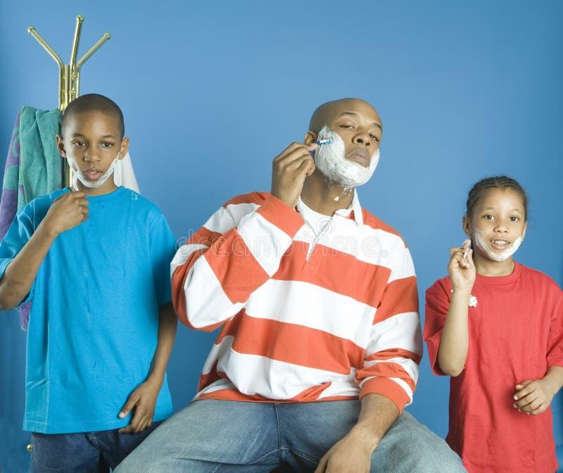 Crianças que copiam seu pai imagens de stock royalty free