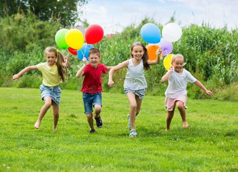 Crianças que correm com balões coloridos foto de stock