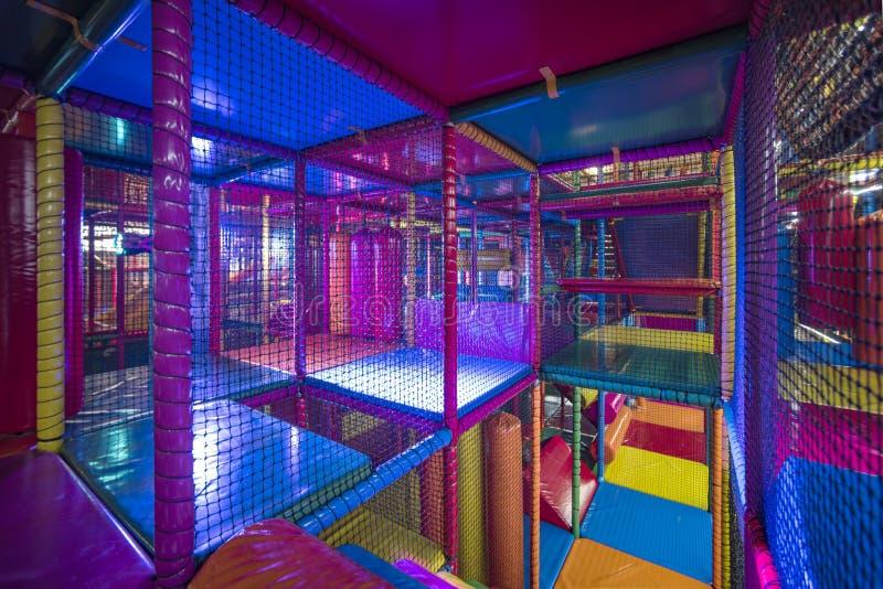 Crianças que correm dentro de um campo de jogos interno colorido fotos de stock