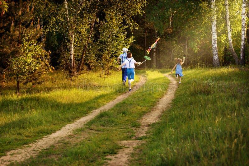 Crianças que correm na natureza no por do sol com raio de luz imagem de stock royalty free