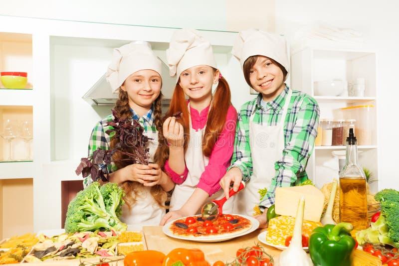 Crianças que cortam a pizza italiana tradicional na cozinha imagem de stock