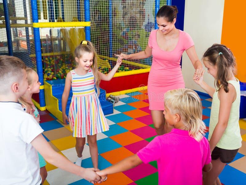 Crianças que dançam com o professor à música na classe na escola foto de stock