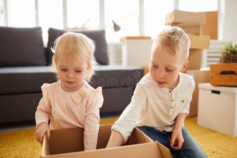 Crianças que desembalam a caixa no plano novo foto de stock royalty free