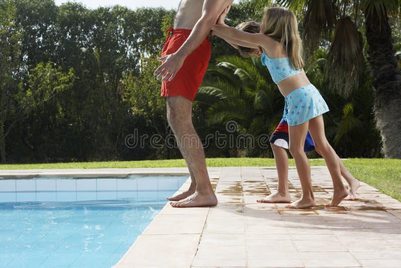 Crianças que empurram o pai Into Swimming Pool imagens de stock royalty free