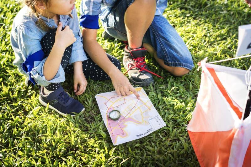 Crianças que encontram o sentido em um mapa fotografia de stock royalty free