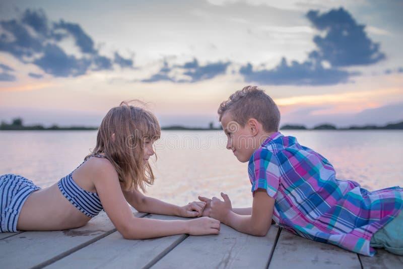 Crianças que encontram-se no cais de madeira e que guardam as mãos imagens de stock