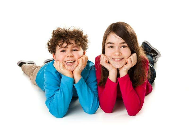Crianças que encontram-se no fundo branco fotos de stock