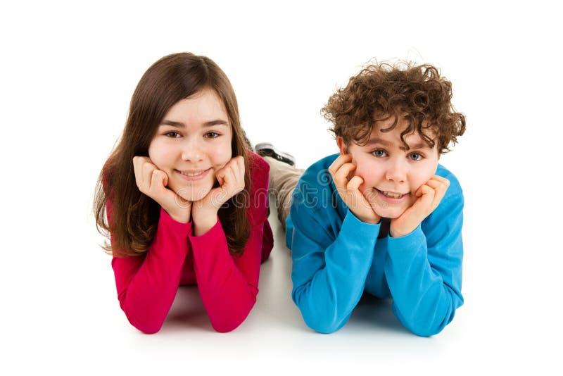 Crianças que encontram-se no fundo branco fotografia de stock