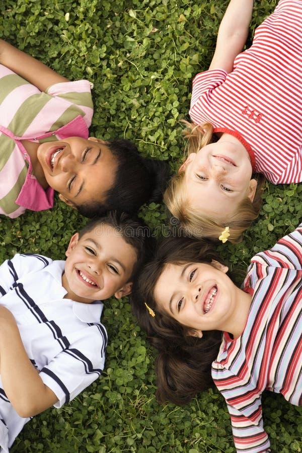 Crianças que encontram-se no trevo com cabeças junto fotos de stock