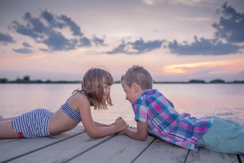 Crianças que encontram-se pelo rio e que guardam as mãos foto de stock royalty free