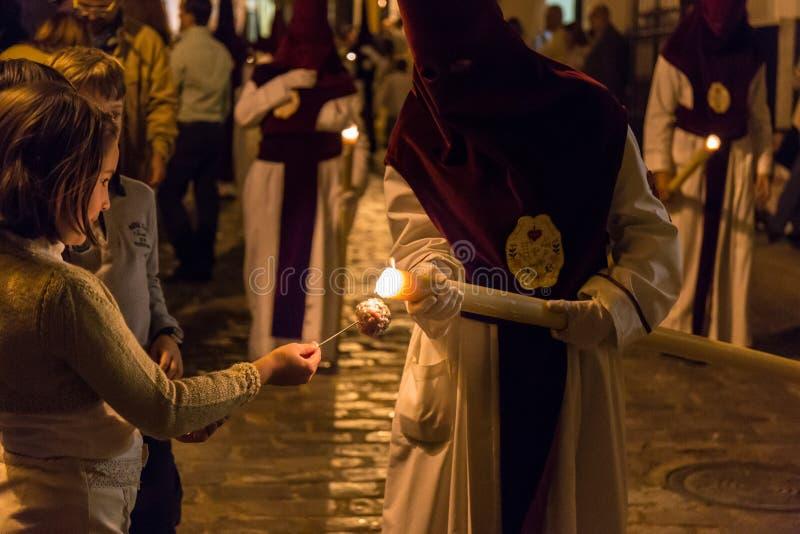 Crianças que escolhem a cera da vela de um Nazarene fotos de stock royalty free