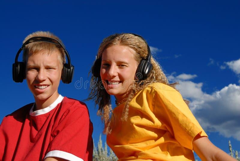 Crianças que escutam a música foto de stock