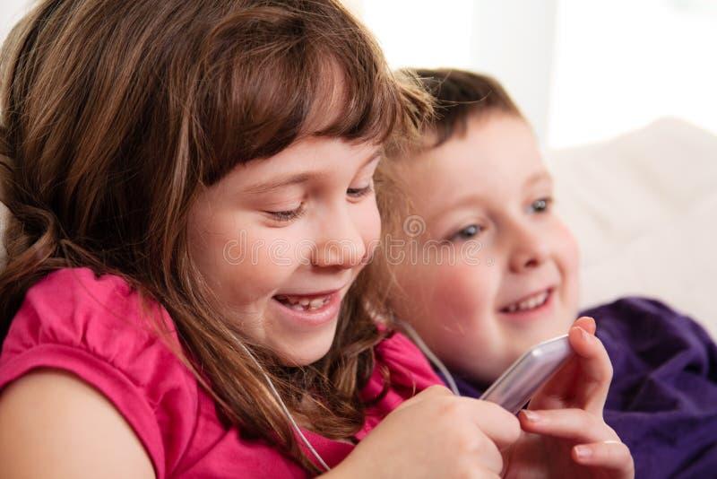 Crianças que escutam a música fotografia de stock