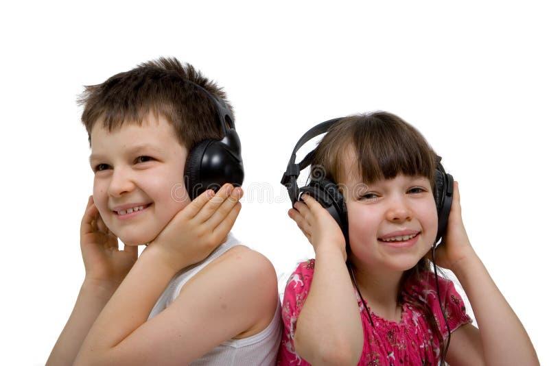 Crianças que escutam a música em auscultadores imagem de stock royalty free