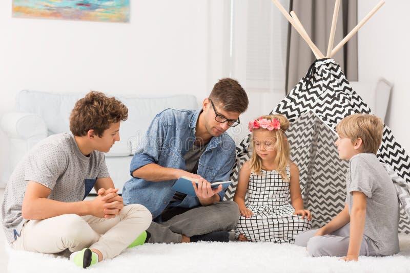 Crianças que escutam sua leitura do paizinho imagem de stock royalty free