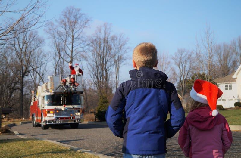 Crianças que esperam Santa em um firetruck foto de stock