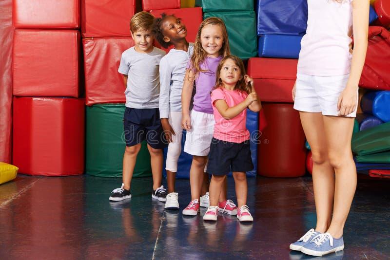Crianças que estão em seguido no gym foto de stock