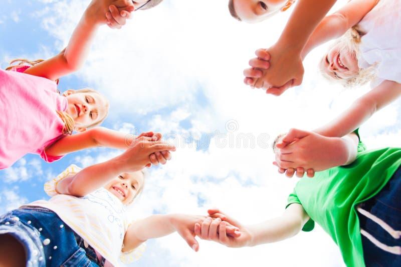 Crianças que estão em um círculo que guarda as mãos, vista inferior imagens de stock