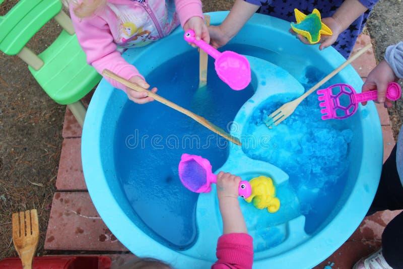 Crianças que exploram a geleia do banho em uma tabela de água imagens de stock royalty free
