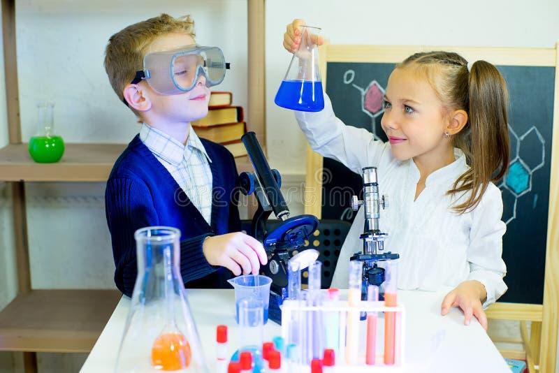 Crianças que fazem experiências da ciência fotos de stock