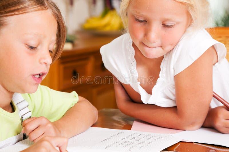 Crianças que fazem trabalhos de casa para a escola fotos de stock royalty free