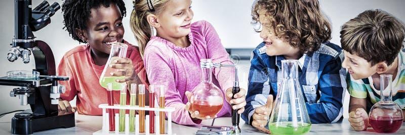 Crianças que fazem uma experiência química no laboratório fotografia de stock