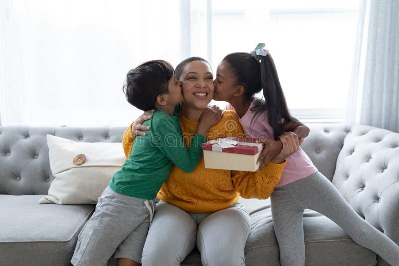 Crianças que felicitam a mãe e que dão sua caixa de presente na sala de visitas fotos de stock royalty free